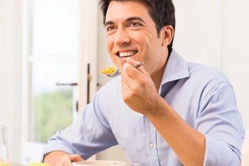 Hombre masticando con implantes dentales